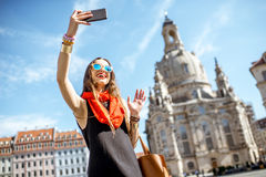 Woman traveling in Dresden city, Germany. Young elegant woman tourist making selfie photo in front of the famous church in Dresden city, Germany stock image