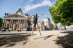 Woman traveling in Dresden city, Germany. Young and happy woman touirst jumping in front of the old university building in Dresden, Germany stock images