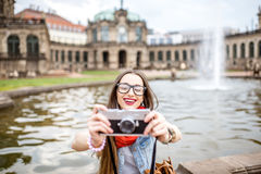 Woman traveling in Dresden city, Germany. Young and happy woman tourist sitting with photo camera on the fountain in the old town of Dresden, Germany royalty free stock photography