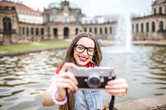 Woman traveling in Dresden city, Germany. Young and happy woman tourist sitting with photo camera on the fountain in the old town of Dresden, Germany stock photos