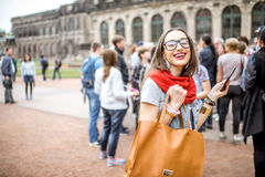 Woman traveling in Dresden city, Germany. Young smiling woman photographing with smartphone while visiting with tourist group the old palace in Dresden city stock image