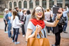 Woman traveling in Dresden city, Germany. Young smiling woman photographing with smartphone while visiting with tourist group the old palace in Dresden city royalty free stock photo