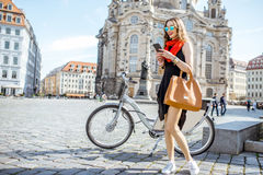 Woman traveling in Dresden city, Germany. Young woman standing with phone and bag near the bicycle on the Neumarkt square in Dresden, Germany royalty free stock image