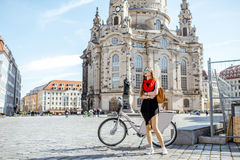 Woman traveling in Dresden city, Germany. Young woman standing with phone and bag near the bicycle on the Neumarkt square in Dresden, Germany stock images