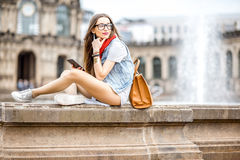 Woman traveling in Dresden city, Germany. Young stylish woman sitting with phone and bag near the fountain in the old town of Dresden, Germany stock photos