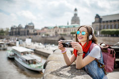 Woman traveling in Dresden city, Germany. Young woman tourist with photo camera enjoying great view from the bridge on the old town of Dresden in Germany stock photo