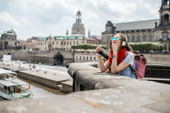Woman traveling in Dresden city, Germany. Young woman tourist with photo camera enjoying great view from the bridge on the old town of Dresden in Germany stock photos