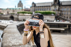 Woman traveling in Dresden city, Germany. Young woman tourist with photo camera enjoying great view from the bridge on the old town of Dresden in Germany royalty free stock image