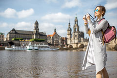 Woman traveling in Dresden city, Germany. Young woman tourist photographing beautiful view on the riverside of the old town of Dresden, Germany stock photography