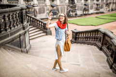 Woman traveling in Dresden city, Germany. Young woman tourist photographing with phone visiting the old palace in Dresden city, Germany royalty free stock photography