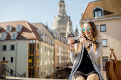 Woman traveling in Dresden city, Germany. Young woman tourist sitting with coffee cup on the famous Bruhl terrace with great view on the old town in Dresden royalty free stock photography