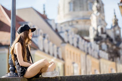 Woman traveling in Dresden city, Germany. Young woman tourist sitting on the famous Bruhl terrace with great view on the old town in Dresden, Germany royalty free stock image