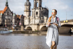 Woman traveling in Dresden city, Germany. Young woman tourist walking with photocamera near the river in the old town of Dresden, Germany royalty free stock photography