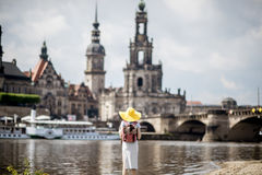 Woman traveling in Dresden city, Germany. Young woman tourist in yellow hat standing back and enjoying great view on the old town of Dresden, Germany royalty free stock images