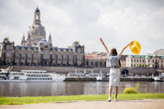 Woman traveling in Dresden city, Germany. Young woman tourist in yellow hat standing back and enjoying great view on the old town of Dresden, Germany royalty free stock photography