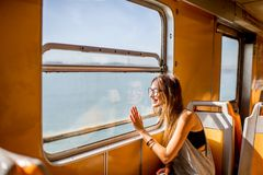 Woman traveling in ferry. Young woman traveling in the old ferry enjoying view on the sea from the window Royalty Free Stock Images