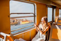 Woman traveling in ferry. Young woman traveling in the old ferry enjoying view on the Lisbon city from the window in portugal Stock Photo