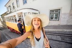 Woman traveling in Lisbon, Portugal. Portrait of a young woman tourist standing near the famous yellow tram traveling in the old town of Lisbon, Portugal stock photo