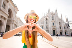 Woman traveling in Milan. Young and happy tourist showing heart with hands in front of the famous Duomo cathedral in Milan. Happy vacations in Milan stock photography