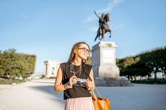 Woman traveling in Montpellier city, France. Portrait of a young happy woman tourist at the famous Peyrou park near the Louis statue during the morning light in royalty free stock images