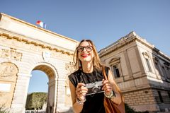 Woman traveling in Montpellier city, France. Portrait of a young happy woman tourist with photo camera in front of the famous Triumphal Arch during the morning stock photography