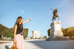 Woman traveling in Montpellier city, France. Portrait of a young woman tourist showing Louis statue at the famous Peyrou park during the morning light in stock photography