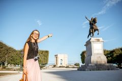 Woman traveling in Montpellier city, France. Portrait of a young woman tourist showing Louis statue at the famous Peyrou park during the morning light in stock photo