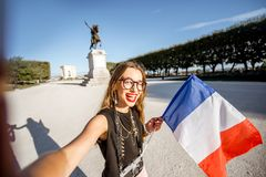 Woman traveling in Montpellier city, France. Young happy woman tourist making selfie photo with french flag at the famous Peyrou park during the morning light in royalty free stock photo