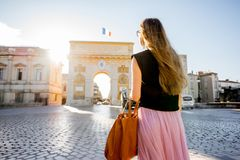 Woman traveling in Montpellier city, France. Young woman tourist enjoying beautiful morning view on the famous Triumphal Arch during the sunrise in Montpellier stock images