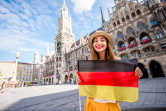 Woman traveling in Munich. Portrait of a young female tourist with german flag standing on the central square in front of the town hall building in Munich Stock Photo