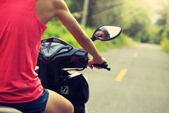 Woman traveling by a scooter on country road Stock Photography