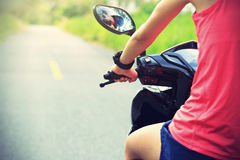 Woman traveling by a scooter on country road Stock Image