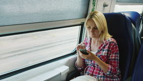 A woman is traveling on the second floor of a train, sitting by the window. Uses a smartphone on the road. 4K video stock video footage