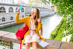 Woman traveling Slovenia. Young female traveler in yellow sweater and sunglasses maling selfie photo with phone sitting on Butchers bridge in the center of Royalty Free Stock Photos