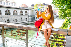 Woman traveling Slovenia. Young female traveler in yellow sweater and sunglasses maling selfie photo with phone sitting on Butchers bridge in the center of Royalty Free Stock Photography