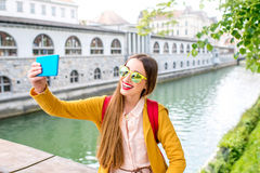 Woman traveling Slovenia. Young female traveler in yellow sweater and sunglasses maling selfie photo with phone sitting on Butchers bridge in the center of Stock Image