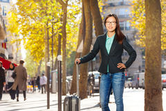 Woman traveling with suitcase standing at street Stock Photo