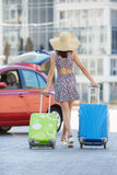 Woman traveling with suitcases,walking on the road. Young happy woman,brunette with long hair,in a large straw hat, in a light summer dress,traveling around Royalty Free Stock Photo