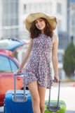 Woman traveling with suitcases,walking on the road. Young happy woman,brunette with long hair,in a large straw hat, in a light summer dress,traveling around Royalty Free Stock Photos