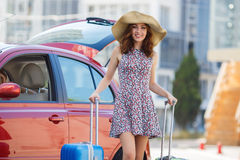 Woman traveling with suitcases,walking on the road. Young happy woman,brunette with long hair,in a large straw hat, in a light summer dress,traveling around Stock Image