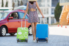 Woman traveling with suitcases,walking on the road. Young happy woman,brunette with long hair,in a large straw hat, in a light summer dress,traveling around Stock Images
