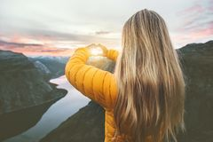Woman traveling in sunset mountains hands heart symbol shaped. Lifestyle emotional concept vacations weekend getaway aerial Norway landscape stock photos