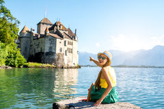 Woman traveling in Switzerland. Young female traveler enjoying great view on Chillon castle sitting on the pier on Geneva lake in Switzerland Royalty Free Stock Image
