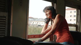 Woman traveling by train looking out the open window stock video footage