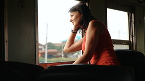 Woman traveling by train looking out the open window stock video