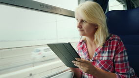 Woman is traveling on a train. Sits by the window, uses a digital tablet. A young woman is traveling on a train. Sits by the window, uses a digital tablet. 4K stock video