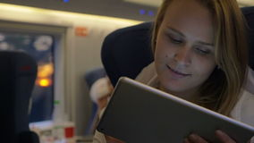 Woman Traveling by Train with Tablet PC. Slow motion shot of a young woman traveling by train and staying in touch with friends using tablet PC on the way stock video