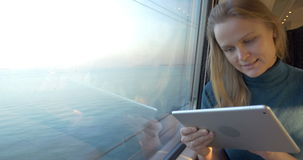 Woman traveling by train and using tablet PC. Dolly shot of a young woman with touch pad sitting by the window in train, which going across the bridge stock video