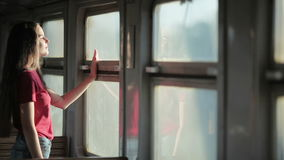 Woman traveling on train. Young brunette woman traveling on train. Girl standing near window, staring into distance stock footage