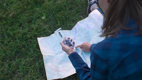 Woman traveling, using map and compass in nature. Woman traveling, using map and compass, searching for road using travel equipment in nature stock video footage